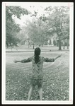 Westbrook College Student in Batik Dress Tossing Leaves, 1970s