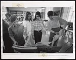 Four Fashion Merchandising Students Consult a Fabric Catalog, Westbrook College, 1970s by Ellis Herwig Photography